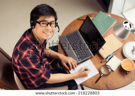 Young Asian man in a headset working on laptop and making notes, view from above - stock photo
