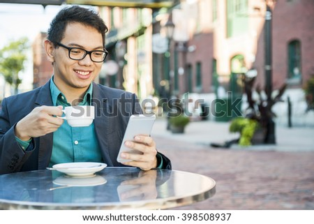 Young asian man in business casual attire sitting and smiling in relaxing outdoor cafe drinking cup of coffee while using mobile phone, copy space. - stock photo