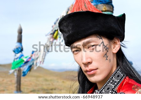 young asian man in national Mongolian suit, his name Chinghis is painted in ancient Mongolian on his face - stock photo