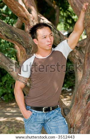 Young Asian man relaxing at the park - stock photo
