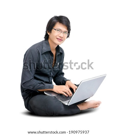 Young asian man sitting on the floor and work with laptop computer - stock photo