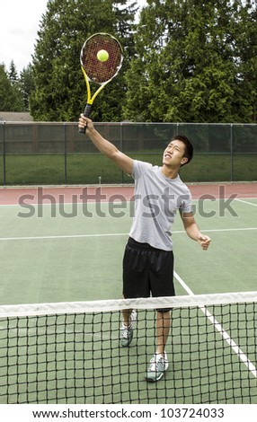 Young Asian Man taking an overhead volley on outdoor tennis court - stock photo
