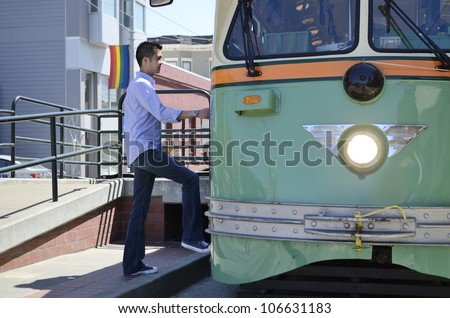Young Asian man wearing a shirt and jeans steps up onto a tram car - stock photo