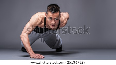 Young asian man workout over grey background - one handed push-up - stock photo