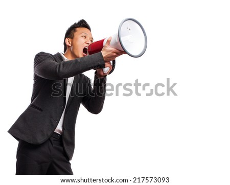 young asian man yelling with a megaphone - stock photo