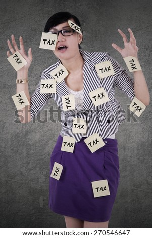 Young asian manager looks stressed with paper notes attached on her body to remind tax time - stock photo
