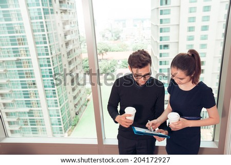 Young Asian managers reading document together - stock photo