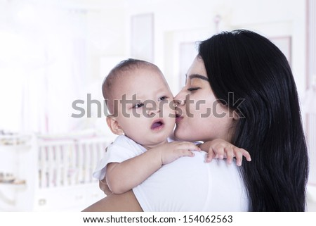 Young asian mother kissing her adorable baby at home - stock photo