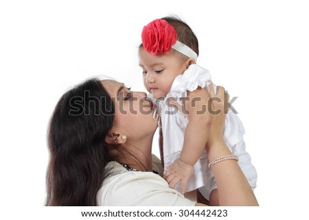 Young Asian mother lift and kiss her baby daughter, isolated on white background - stock photo