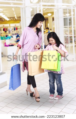 Young asian mother looking at her daughter's shopping bags in the mall - stock photo