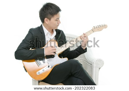 Young Asian musician playing a guitar - stock photo