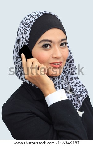 Young asian muslim business woman talking to the mobile phone while looking to the camera - stock photo