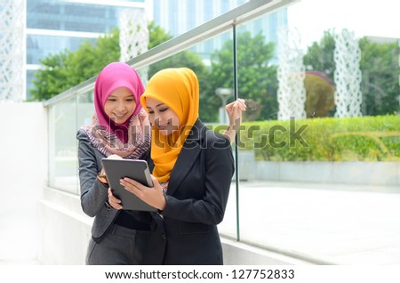 Young asian muslim businesswomen in head scarf smile with mobile laptop - stock photo