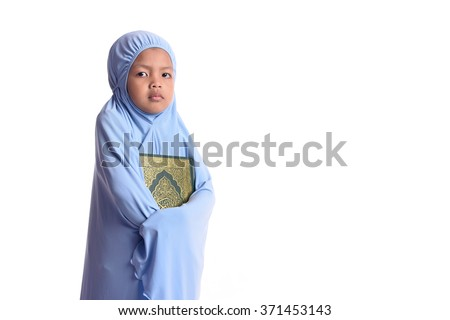 Young Asian Muslim girl in blue hijab hold Al Quran - stock photo