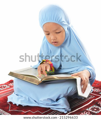 Young Asian Muslim girl in blue hijab reading Al Quran on a prayer mat over white background. - stock photo