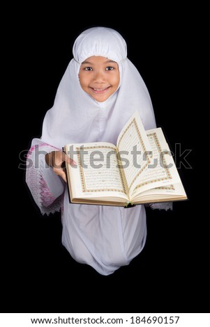 Young Asian Muslim in white hijab read Al Quran over black background - stock photo