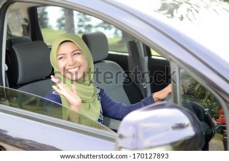 Young asian muslim woman in head scarf smile inside the car wave hand to friend - stock photo