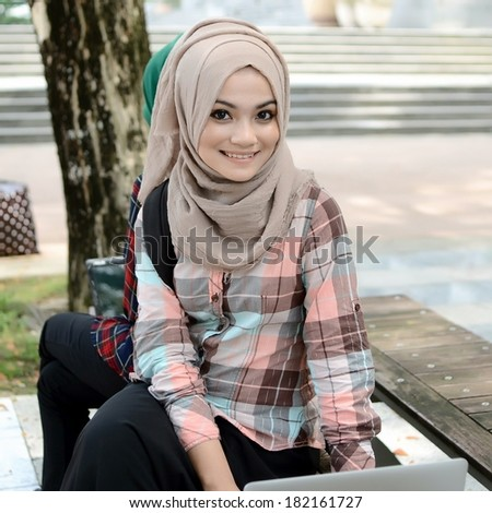 Young asian muslim woman in head scarf smile while sitting with friend - stock photo