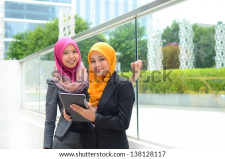 Young asian muslim woman in head scarf smile with mobile laptop - stock photo