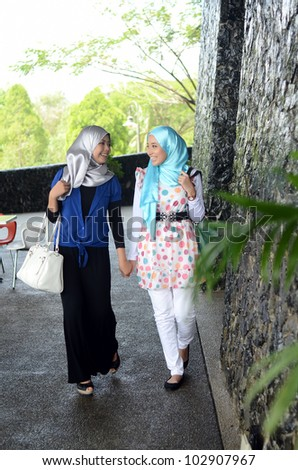 Young asian Muslim woman in head scarf walk together with handbag - stock photo
