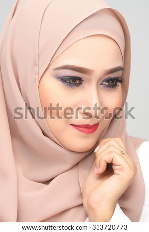 young asian muslim woman with expression wearing hijab - stock photo