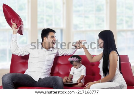 Young asian parents quarreling at home between their baby on sofa - stock photo
