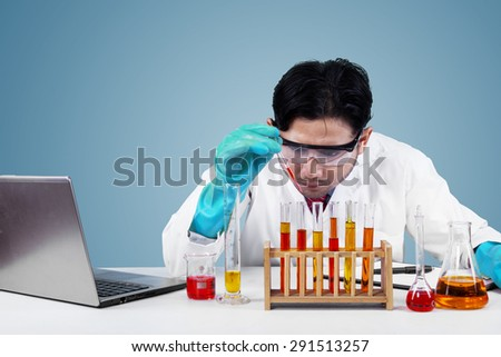 Young asian scientist makes chemical experiment seriously in the laboratory - stock photo
