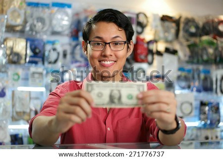 Young asian shop owner in computer store, showing his first dollar to the camera and smiling. Focus on face  - stock photo