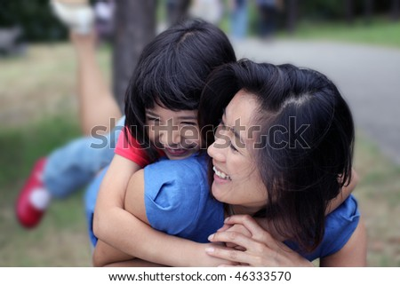 Young Asian sisters outdoors having fun - stock photo