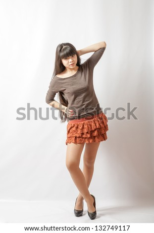 Young asian student. Beautiful young woman. Portrait of asian woman in brown skirt full body shot - stock photo