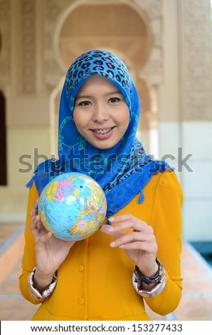 Young asian student muslim woman in head scarf smile holding world ball - stock photo