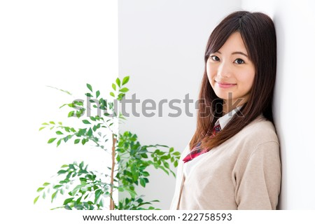 young asian student relaxing in the white room  - stock photo