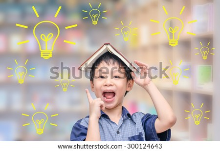 Young Asian student thinking with light bulbs in library - stock photo