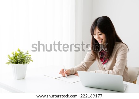 young asian student using laptop computer in the white room - stock photo