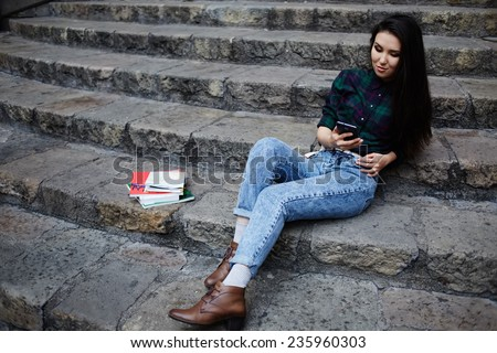 Young asian student using mobile phone during her class break at university school sitting on the steps, student girl browsing the internet with her cell phone, technology and communication concept - stock photo