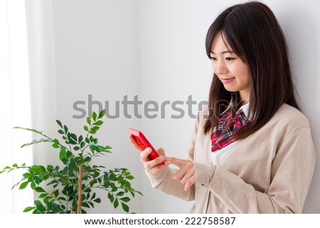 young asian student using smart phone in the white room  - stock photo