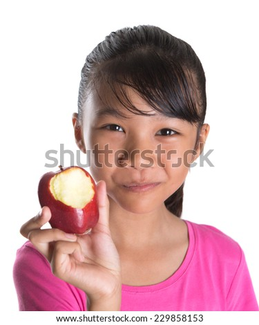 Young Asian teen eating a red apple over white background - stock photo