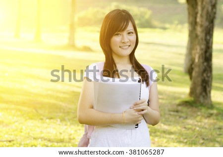 Young Asian teen student standing on campus lawn, holding books and smiling. - stock photo