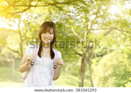 Young Asian teen student standing on campus lawn, with backpack and smiling. - stock photo