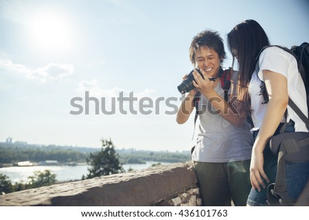 Young Asian Tourists Looking At The Photo - stock photo