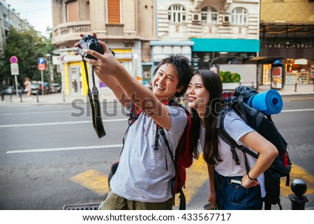 Young Asian Tourists Taking A Selfie - stock photo