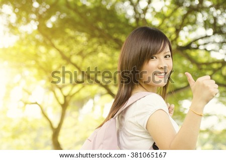 Young Asian university girl student standing on campus lawn, giving thumb up and smiling. - stock photo