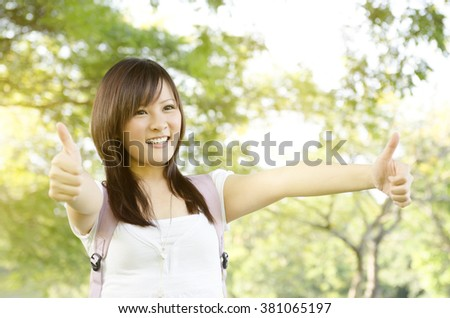 Young Asian university girl student standing on campus lawn, showing thumbs up and smiling. - stock photo