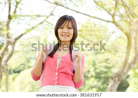 Young Asian university girl student standing on campus lawn, with backpack and smiling. - stock photo