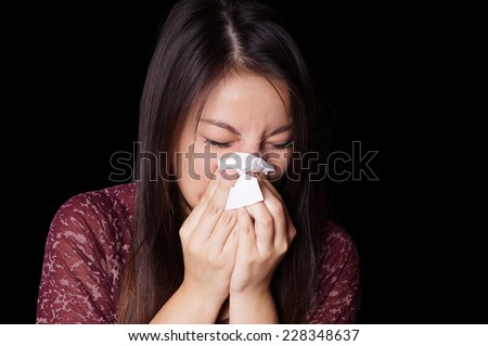 young asian woman blowing her nose with paper tissue - stock photo