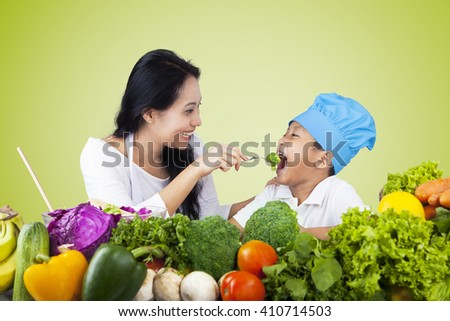 Young Asian woman feeding her son with fresh vegetables using fork after cooking together - stock photo