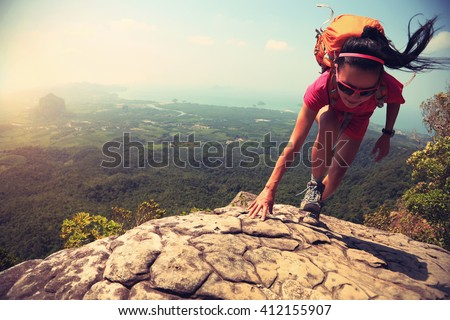 young asian woman hiker climbing rock on mountain peak cliff - stock photo