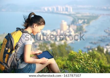 young asian woman hiker use digital tablet seaside mountain peak  - stock photo