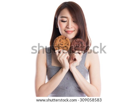 Young asian woman holding and  eating two chocolate chip cookies, isolated on white background. - stock photo