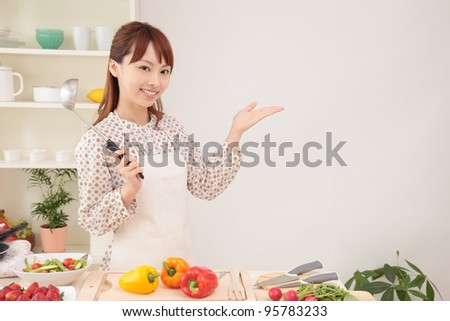 Young Asian woman holding hands in the kitchen - stock photo